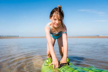 belle jeune fille jouant avec son crocodile gonflable