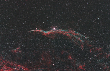 Close up of Veil Nebula in the dark space and with many stars as background. In the middle there is also the star 52 Cygni.