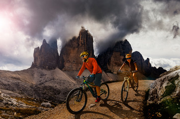 Couple cycling on electric bike, rides mountain trail. Woman and Man riding on bikes in Dolomites...