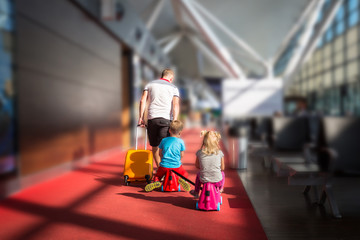 Father with two children in the airport terminal fly together on vacation