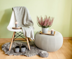 Plastic chair with wood legs covered with gray wool plaid, knitted pattern plastic table, fake sheepskin rug with felt slippers and heather in flower pot, against pale green wall.