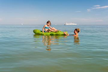 maman et sa fille jouant dans la mer