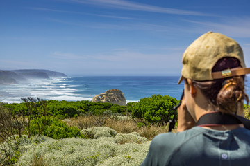 A woman taking a picture in Castle Rock, Port Campbell National Park, Victoria, Australia. Great Ocean Road. Scenic Coastal Route.