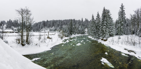 Snowy winter in the Carpathians. Mountain river Prut and snow forest.