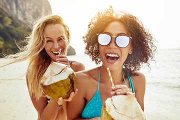 Two laughing friends drinking from coconuts on a sandy beach Wall mural