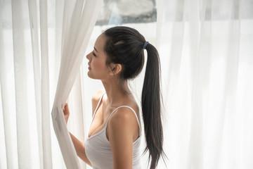 Attractive sexy asian woman standing near balcony window.