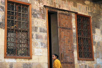 A young woman stands in front of an old wooden door by a historic house in Darb al-Ahmar neighbourhood in Cairo