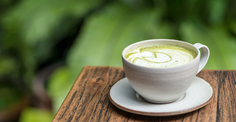 Horizontal shot of matcha latte in a white cup on wooden table. Matcha refers to finely-milled Japanese green tea. This type of latte is a creamy, delicious, antioxidant-filled drink.