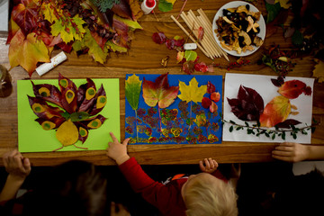 Children, applying leaves using glue, scissors, and paint, while doing arts and crafts in school.