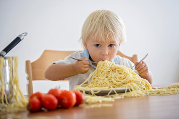 Little baby boy, toddler child, eating spaghetti for lunch and making a mess at home