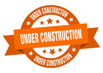 under construction ribbon. under construction round orange sign. under construction