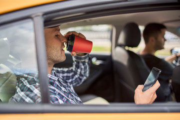 Picture of man with phone and glass of coffee sitting in back seat in taxi