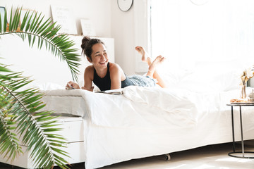 Acrylic Prints Relaxation Portrait of pretty woman smiling while lying and reading magazine on bed in bright room with green plant