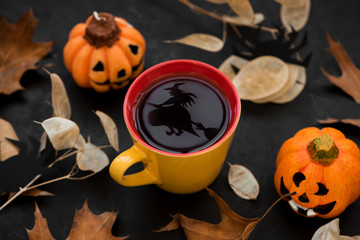Cup of tea with reflection of witch on broomstick on dark wooden background. Halloween celebration concept. Copy space