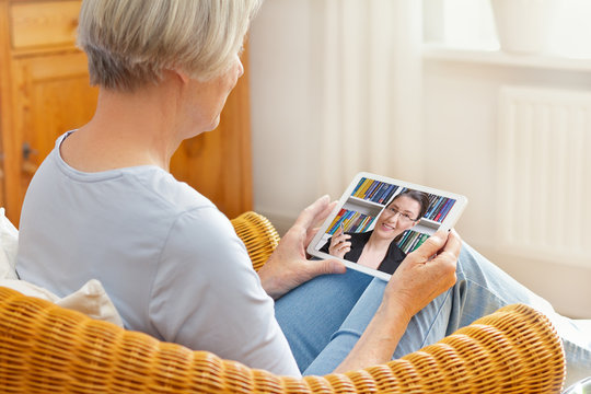 Teletherapy concept, senior woman talking with her teacher, counselor or laywer during a live call on her tablet pc at home