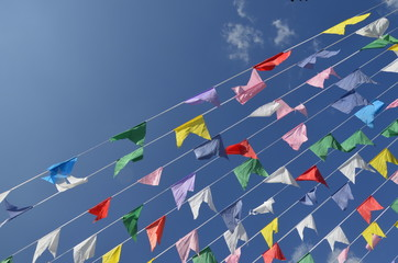 multicolored flags on blue sky background and white clouds. pink, yellow, red, white, blue, green