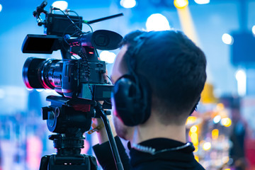 Video operator. Videography.Filming.A man is shooting a video.The work of a videographer. Shooting with a professional camera with a tripod. A man shoots on a professional video camera.Videographer