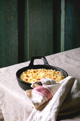 Classic american dish baked mac and cheese in cast iron pan with towel on kitchen table with linen tablecloth. Dark rustik style