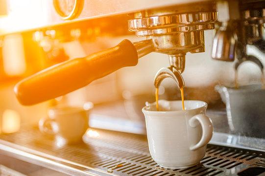 Close-up of espresso pouring from coffee machine. Barista make coffee latte art with espresso machine in cafe  sunrise color tone.