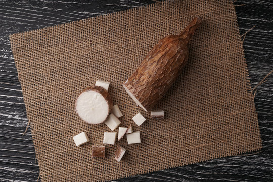 Sliced yucca root on a sackcloth on a black wooden table