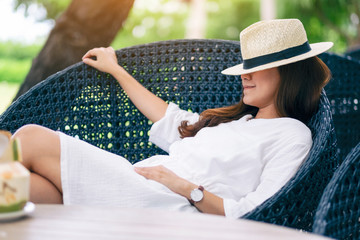 Portrait image of a beautiful asian woman with hat lying down on a bench in the garden with coconut on the table