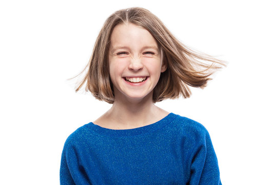 Cute teen girl in a blue sweater is laughing. Isolated over white background.