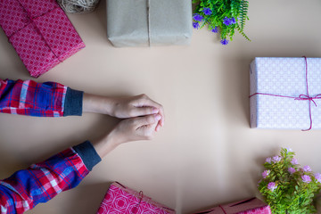 The girl's hand with the gift box placed on the table. happy time concept