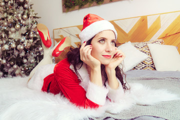young beautiful girl in red Santa Claus suit is lying on the bed and dreamily looking into distance against background of apartment decorated for Christmas..