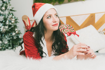 Funny Christmas Girl Holding a Candy Lollipops. Beautiful expressive woman in sweet Christmas fantasy portrait with lollipops