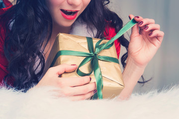 Christmas woman portrait hold christmas gift. Smiling happy girl on Christmas tree background. young woman opens Christmas gift.