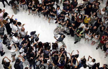A man holds up a tuba as protesters shout slogans and sing Hong Kong's anthem during a protest at New Town Plaza shopping mall in Hong Kong