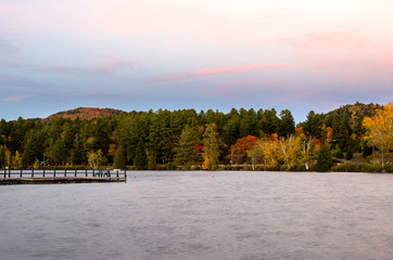 Lake surrounded by colourful autumn trees at twilight. A deserted wooden jetty is visible in foreground on the left side of the picture.