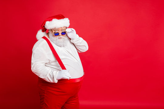 Portrait of handsome old funny fat overweight santa claus with big belly touch his retro specs choose naughty kids wear trousers pants isolated over red background