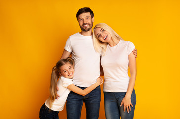 Happy Family Hugging Posing Over Yellow Background