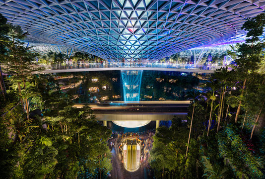 The Jewel at Changi Airport, with the rain vortex indoor waterfall illuminated during the light show, Singapore