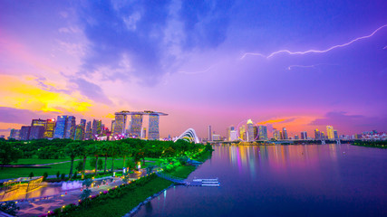 Royalty-free stock photo ID: 1488208352  Landscape of Singapore city during the twilight time and thunderbolt with marina bay sand tower, and Singapore flyer and Gardens by the Bay background. Tourist