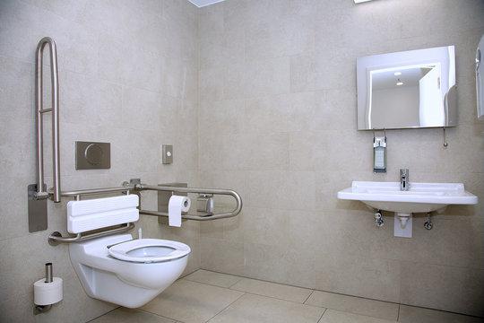 Behindertengerechte Toilette mit unterfahrbarem Waschbecken und Abstützmöglichkeiten