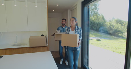 Couple Carrying Boxes Into New Home On Moving Day.
