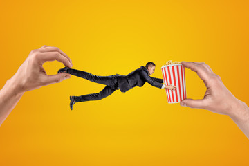 Big male hand holding tiny businessman who is reaching to another big hand holding popcorn bucket on yellow background