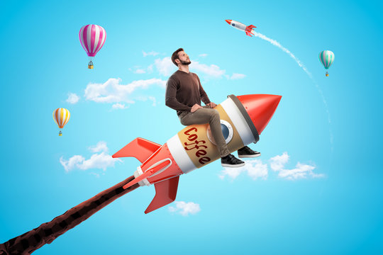 Confident young man riding toy rocket made of coffee cup in blue sky with hot air balloons and rocket in background.