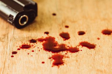 Close up of red blood with gun on wooden table, conceptual image suicide prevention concept, copy space