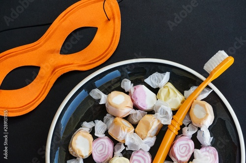 Colorful Halloween sweets with mask and toothbrush, dentist's message concept