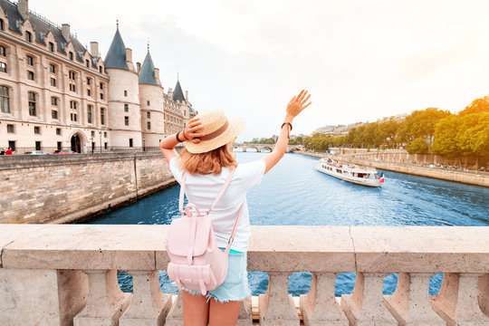 A girl tourist in a hat standing on a bridge and waving to a river cruise sailing by Seine river in Paris
