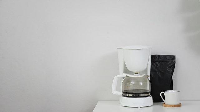 Coffee machine, coffee mug and black bag on copy space table.