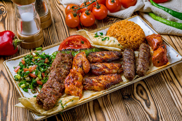 assorted kebabs with bulgur and vegetables Turkish cuisine on wooden table