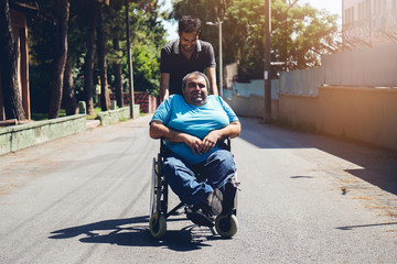 Happy man in wheelchair and him friend outdoors