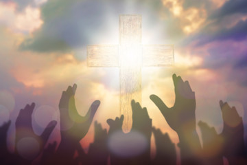 Blurred of Christian Congregation hands Worship God together in front of wooden cross in cloudy sky, conceptual image of praise and worship