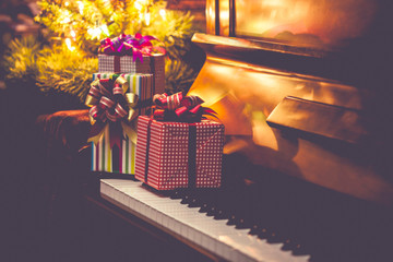 Christmas gift boxes on piano keys  with Christmas tree as backgroundin the night, Vintage tone