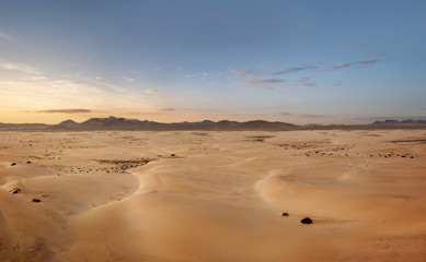 High angle, panoramic view of an empty desert at the sunset with copy space