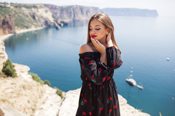 Young beautiful woman with perfect makeup is wearing fashion dress on the cliff of mountain with the blue sea view, travel concept